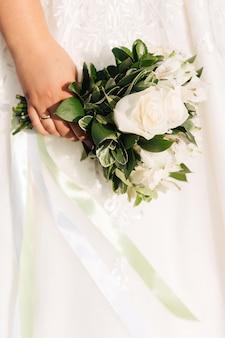 De bruid houdt een boeket witte rozen op de achtergrond van een witte trouwjurk.