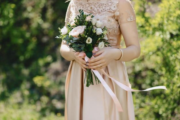 De bruid houdt een bruidsboeket in haar handen