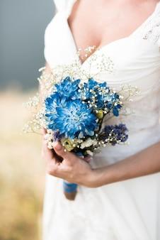 De bruid houdt een bruidsboeket vast met blauwe bloemen