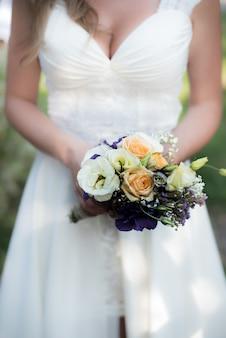 De bruid houdt een bruidsboeket vast met paarse bloemen