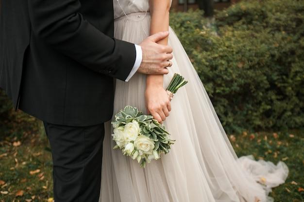 De bruid houdt een bruidsboeket vast.