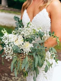 De bruid houdt een bruiloftsaccessoire in haar handen - een boeket gemaakt van rozen