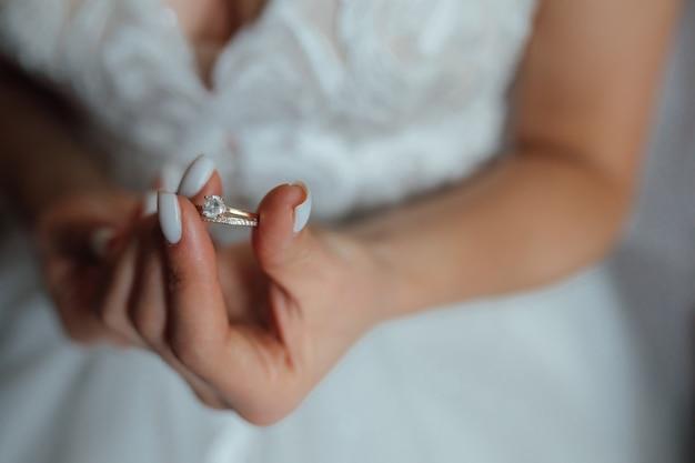 De bruid houdt een gouden trouwring vast met een diamant