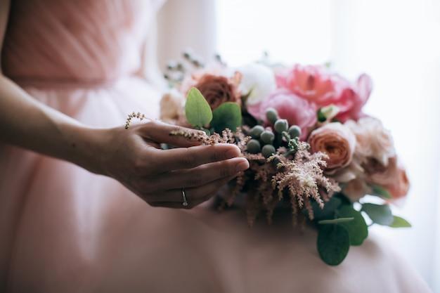 De bruid houdt een mooi roze boeket in haar handen