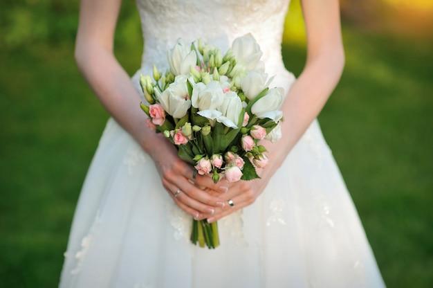 De bruid houdt een mooi wit huwelijksboeket