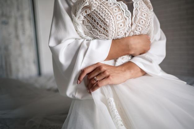De bruid houdt een witte jurk in haar handen op de trouwdag.