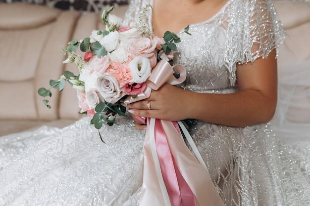 De bruid houdt het bruidsboeket met witte en roze rozen en ander bloemendecor