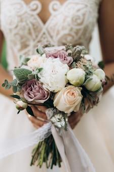 De bruid houdt het mooie bruids boeket, omhoog sluit