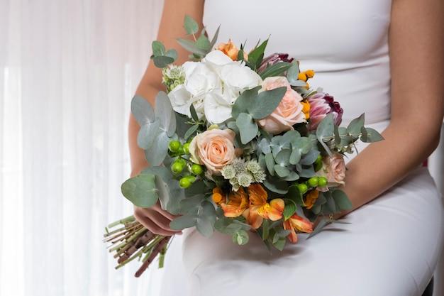 De bruid houdt huwelijksboeket van verschillende kleuren in een huwelijksviering