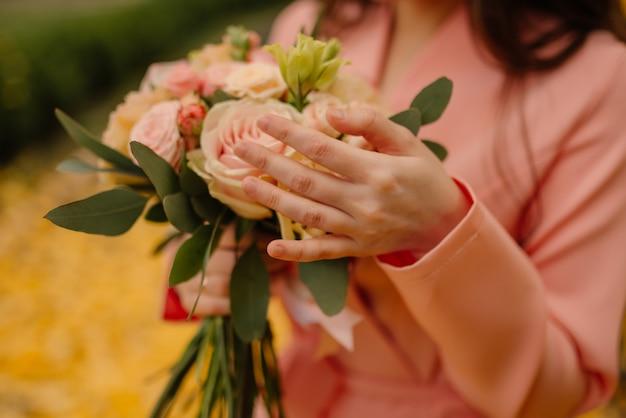 De bruid houdt in haar handen een huwelijksboeket