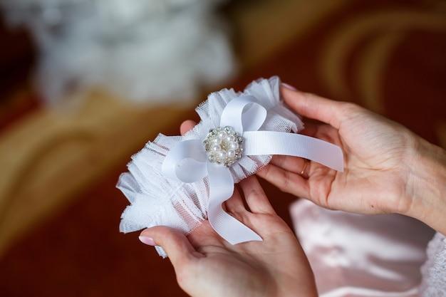 De bruid houdt in haar handen een kousenband op haar been