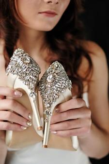 De bruid houdt trouwschoenen in haar handen. schoenen close-up