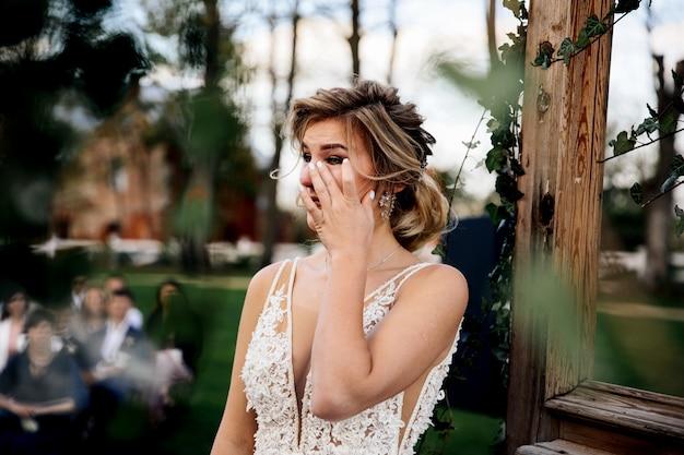 De bruid huilt luisterend de huwelijksgelofte van de bruidegom