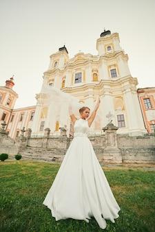 De bruid in een chique jurk dwarrelt rond in de buurt van de kerk