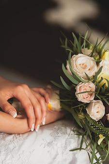 De bruid in een elegante opengewerkte trouwjurk heeft een prachtig bruidsboeket van witte of beige rozen en groene bladeren. handenmeisjes met zacht keurig manicureclose-up. bruiloft thema