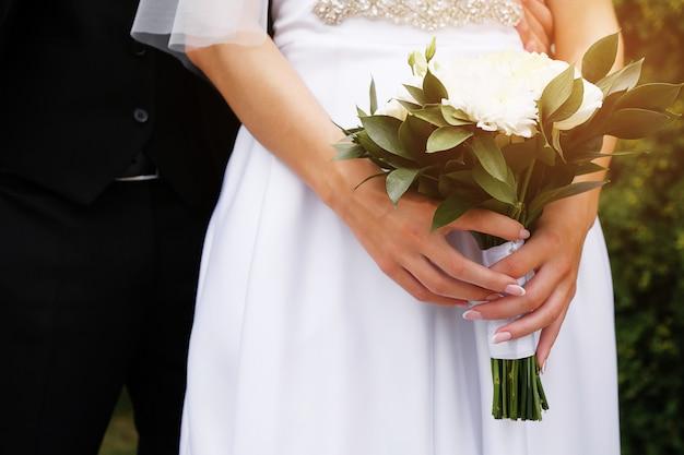 De bruid in een elegante trouwjurk heeft een mooi boeket witte rozen en chrysanten en groene bladeren. omarm de jonggehuwden, de handen van de bruid en bruidegom close-up, buitenshuis.