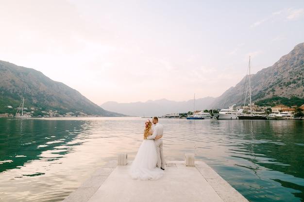 De bruid in een krans en bruidegom knuffelen op de pier bij het oude centrum van kotor in de baai van kotor