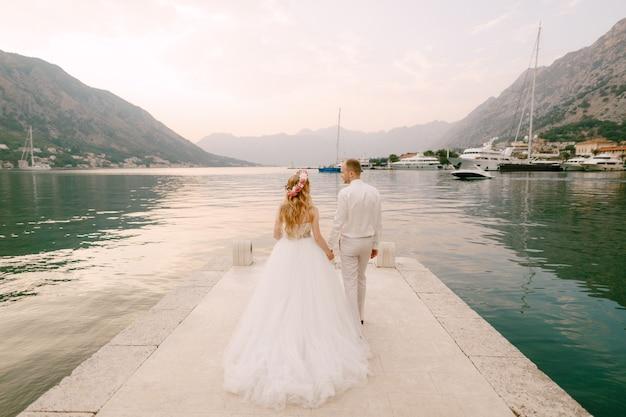 De bruid in een krans en de bruidegom lopen hand in hand langs de pier in de buurt van het oude centrum van kotor in de