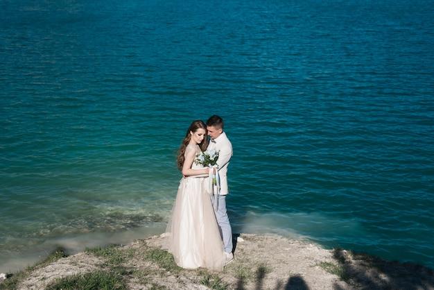 De bruid in een mooie jurk knuffelen de bruidegom in een licht pak in de buurt van het meer. bruidspaar staande op een zanderige heuvel in de open lucht. een romantisch liefdesverhaal. azuurblauw water aan de horizon.