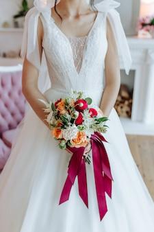 De bruid in een mooie witte jurk met een boeket in haar handen