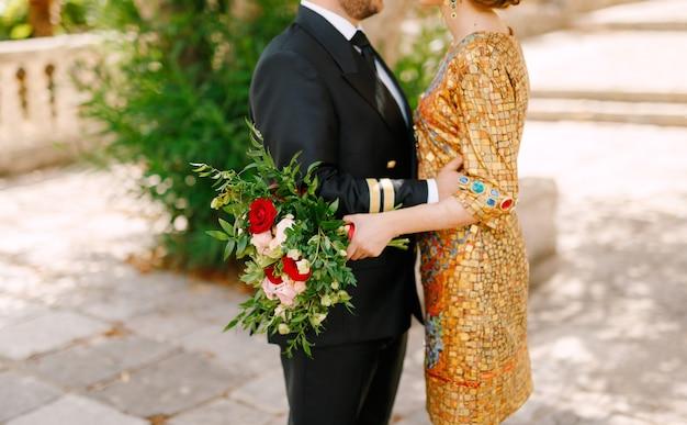 De bruid in een ongebruikelijke gouden jurk en de bruidegom in een pak omhelzen het boeket van de bruid