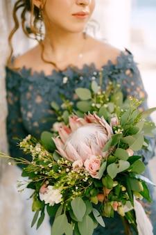 De bruid in een stijlvolle blauwe jurk met bruiloft boeket in de oude binnenstad van perast close-up