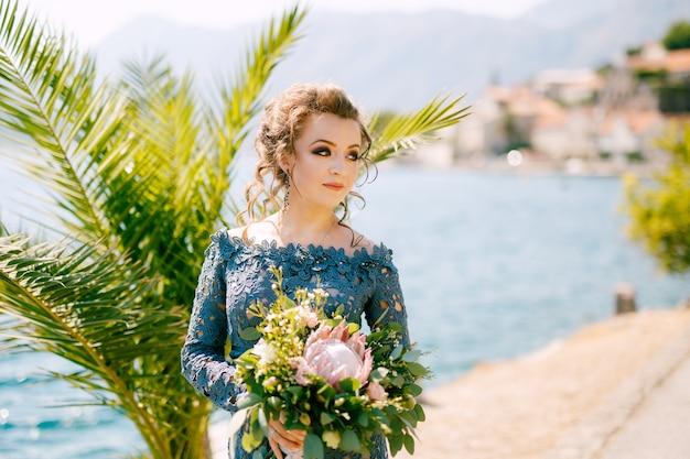 De bruid in een stijlvolle grijze jurk staat met bruidsboeketten op de pier in de buurt van het oude centrum van perast