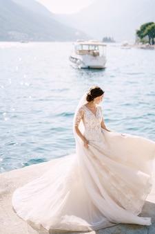 De bruid in een trouwjurk danst op de pier en zwaait met een jurk