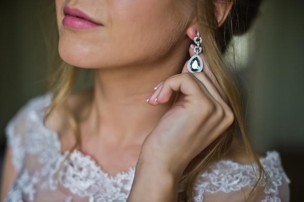 De bruid in een trouwjurk draagt oorbellen
