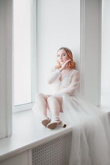 De bruid in een wit transparant negligé met een lange sleep zit met haar voeten op de vensterbank