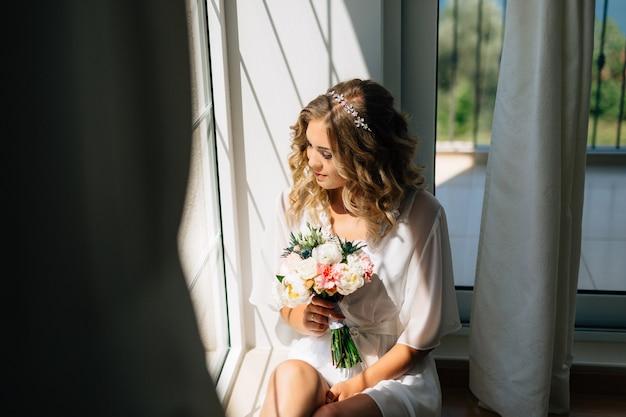 De bruid in een witte peignoir zit bij het raam met een bruidsboeket in haar handen