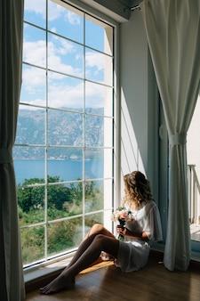 De bruid in een witte peignoir zit bij het raam met uitzicht op de baai van kotor met een bruidsboeket