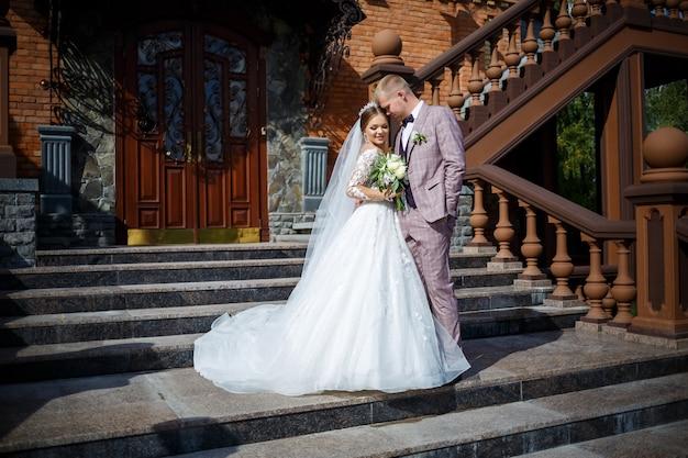 De bruid in een witte trouwjurk en bruidegom in een pak op de achtergrond van een bakstenen gebouw met grote treden