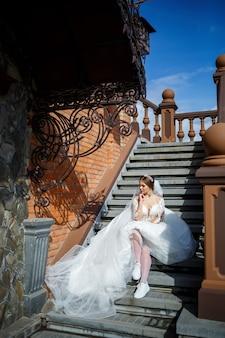 De bruid in een witte trouwjurk en witte sneakers zit op de trappen van een groot gebouw