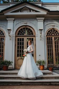 De bruid in een witte trouwjurk staat bij het kasteel.