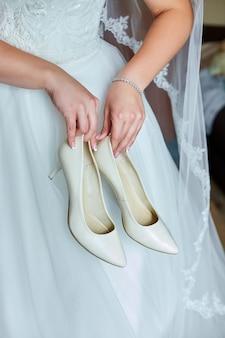 De bruid in haar trouwjurk houdt thuis haar stijlvolle beige schoenen in haar hand