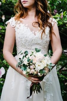 De bruid in jurk houdt een bruidsboeket vast van pastel, roze, witte pioenrozen, rozenbloemen, groen en versierd met lint.