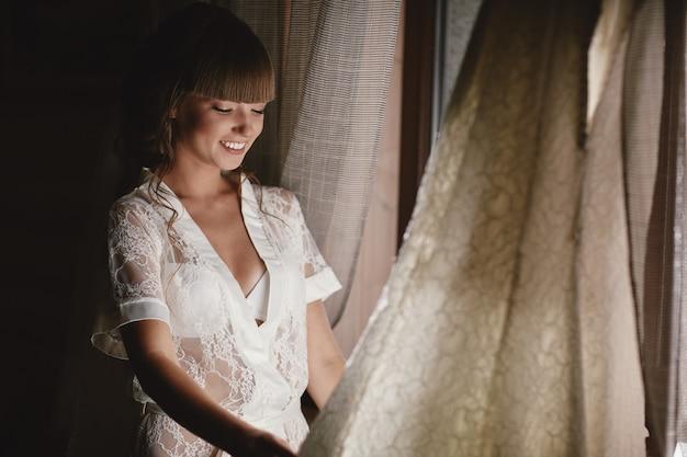 De bruid in sexy ondergoed of nachtjurk van de sluier op haar hoofd zit thuis in de kamer op de fauteuil