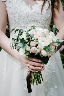 De bruid in witte jurk houdt een boeket van pastel, roze, witte pioenrozen, rozenbloemen, groen en versierd met lint vast.