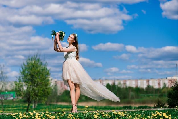 De bruid in witte trouwjurk houdt een boeket in groen park. zomerhuwelijk op een zonnige dag.