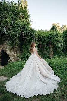 De bruid is in een prachtige jurk in de natuur