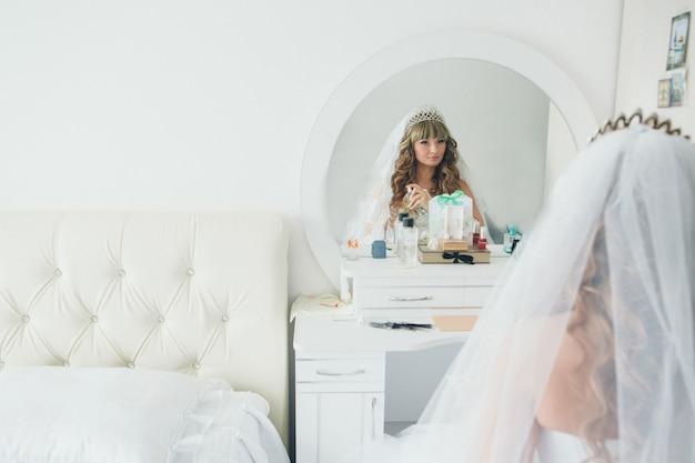 De bruid kijkt in de spiegel en gebruikt parfum in de witte kamer