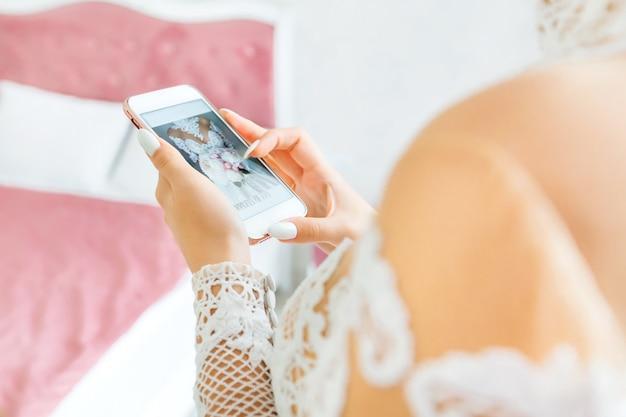 De bruid kijkt naar de telefoon met haar foto in een lichte kamer