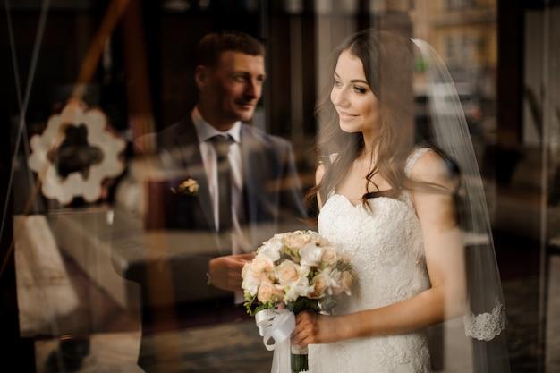 De bruid kijkt uit het raam naar de weerspiegeling van de bruidegom