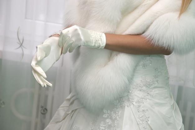 De bruid kleedt bruidshandschoenen