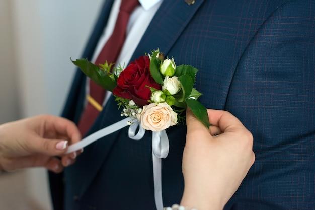 De bruid knoopt een bloemenboutonnière aan de bruidegom op het jasje