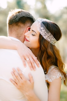 De bruid knuffelt zachtjes de bruidegom in het park en glimlacht close-up