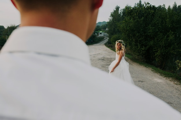 De bruid leidt bruidegom op de weg