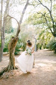 De bruid loopt tussen de bomen in een pittoresk park en houdt een boeket in haar handen