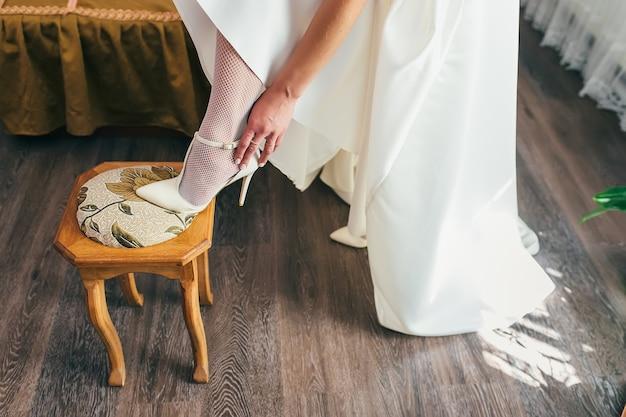 De bruid maakt de bruidsschoen vast aan de stoel
